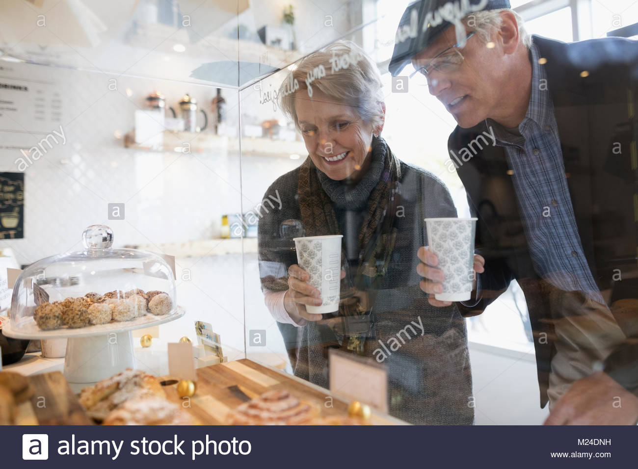 Senior couple drinking coffee and eyeing pastries at cafe - Stock Image
