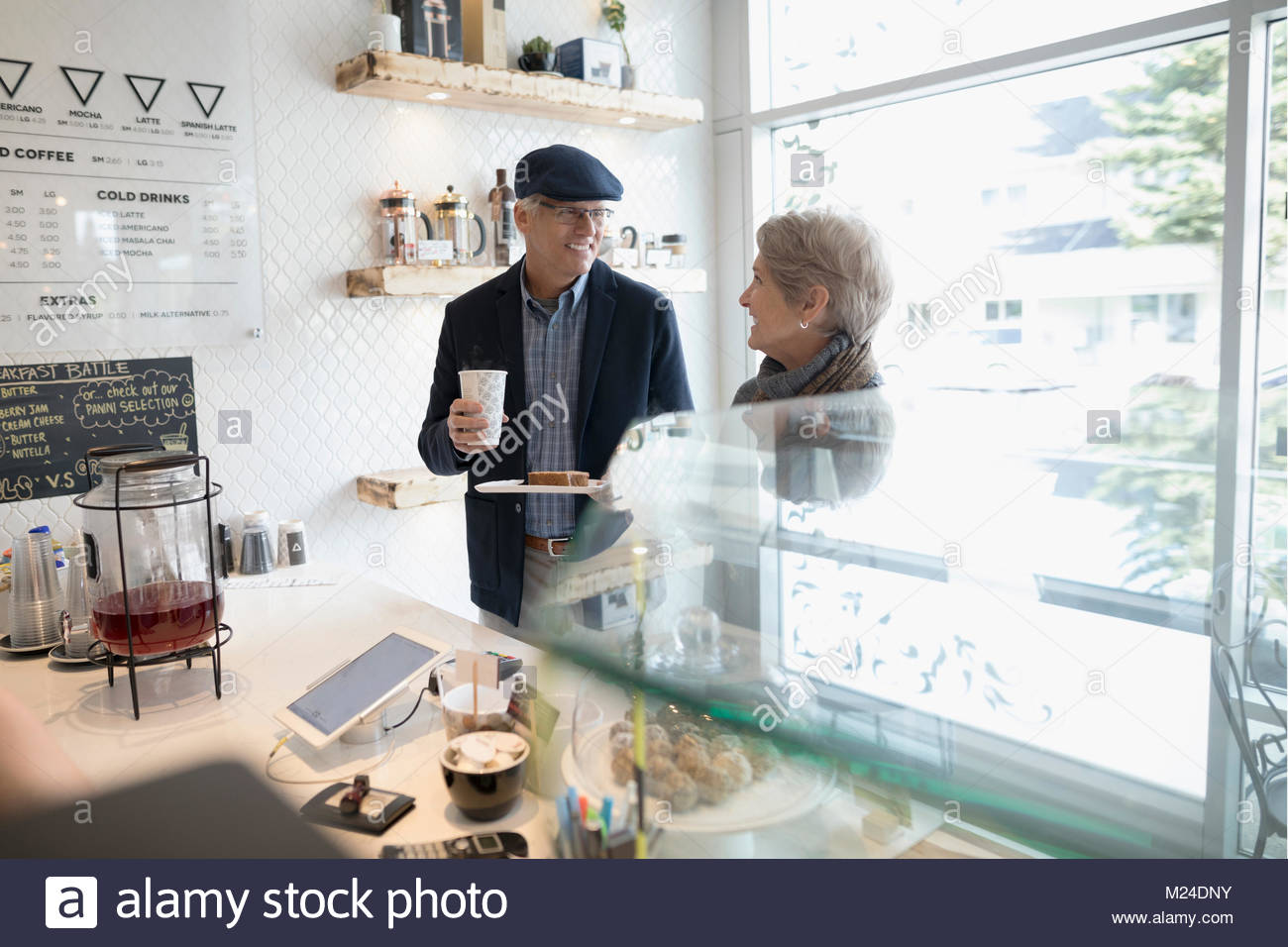 Senior couple buying coffee and pastries at cafe counter - Stock Image