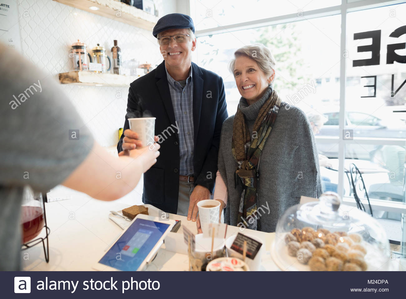 Smiling senior couple buying coffee at cafe counter - Stock Image