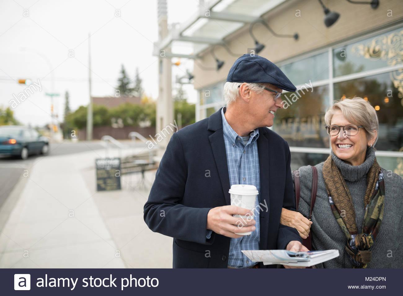 Smiling senior couple drinking coffee, walking outside sidewalk cafe - Stock Image