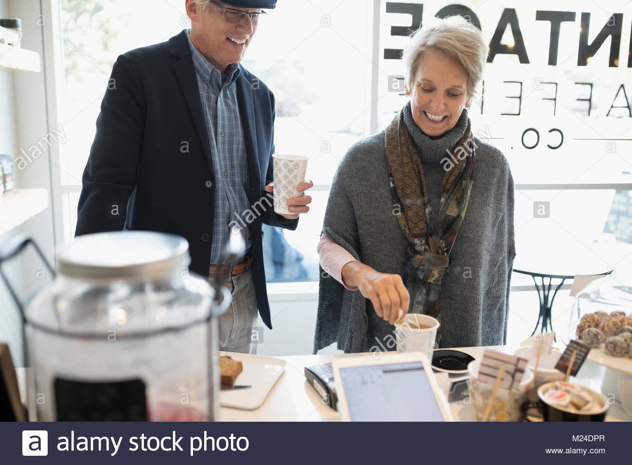 Smiling senior couple buying coffee and pastries at cafe counter - Stock Image