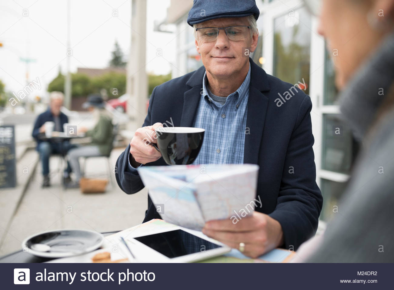 Senior man drinking coffee and looking at map at sidewalk cafe - Stock Image