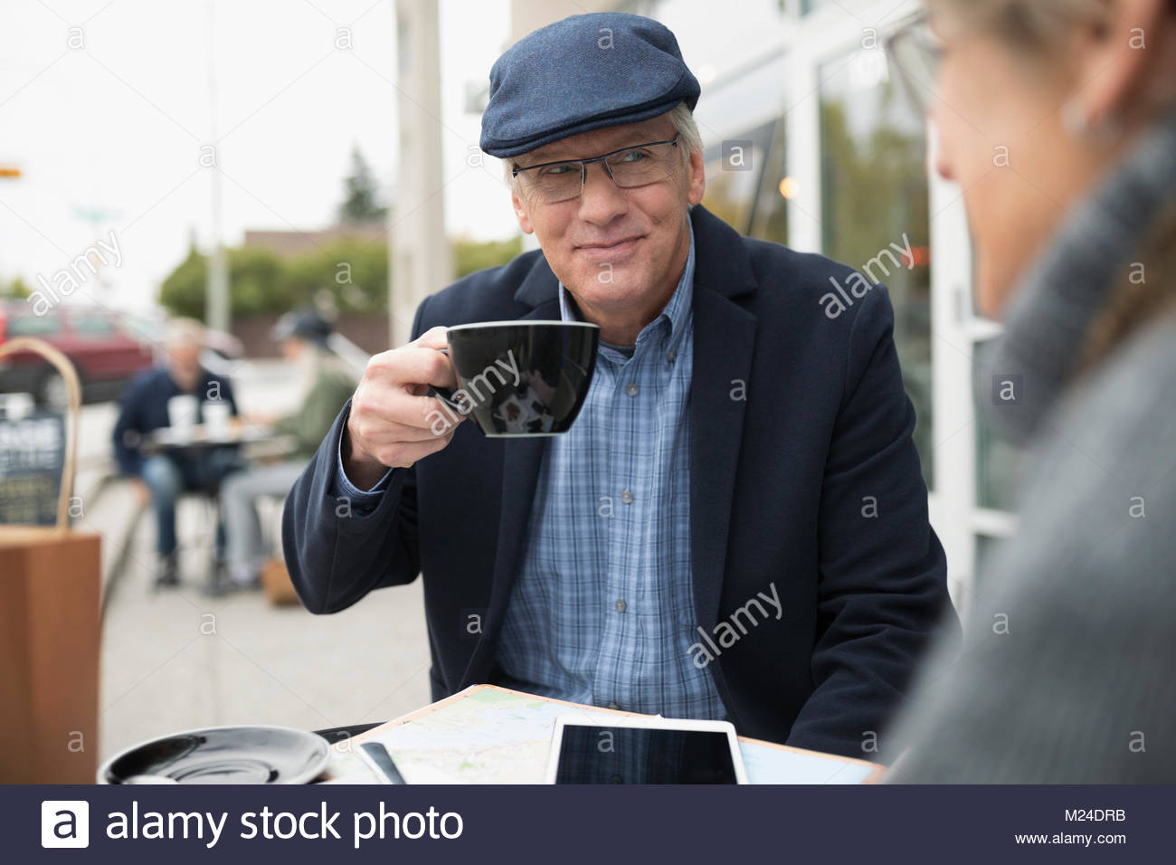 Senior man drinking coffee and talking to wife at sidewalk cafe - Stock Image