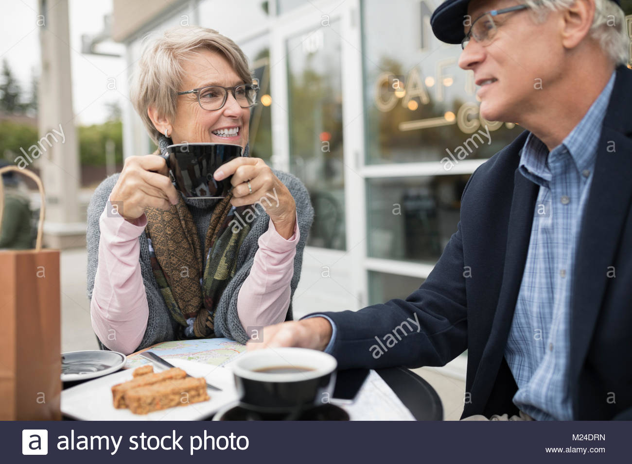 Senior couple talking and drinking coffee at sidewalk cafe - Stock Image