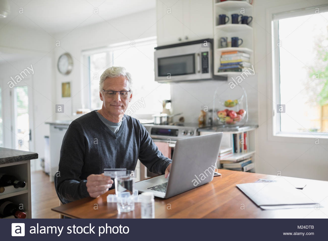 Senior man with credit card reordering prescription medication at laptop in kitchen - Stock Image