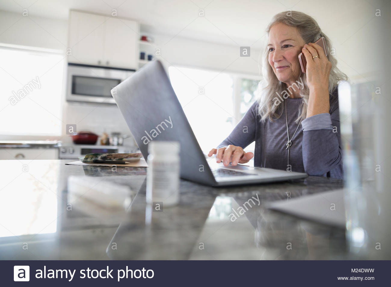 Senior woman talking on cell phone and using laptop in kitchen - Stock Image
