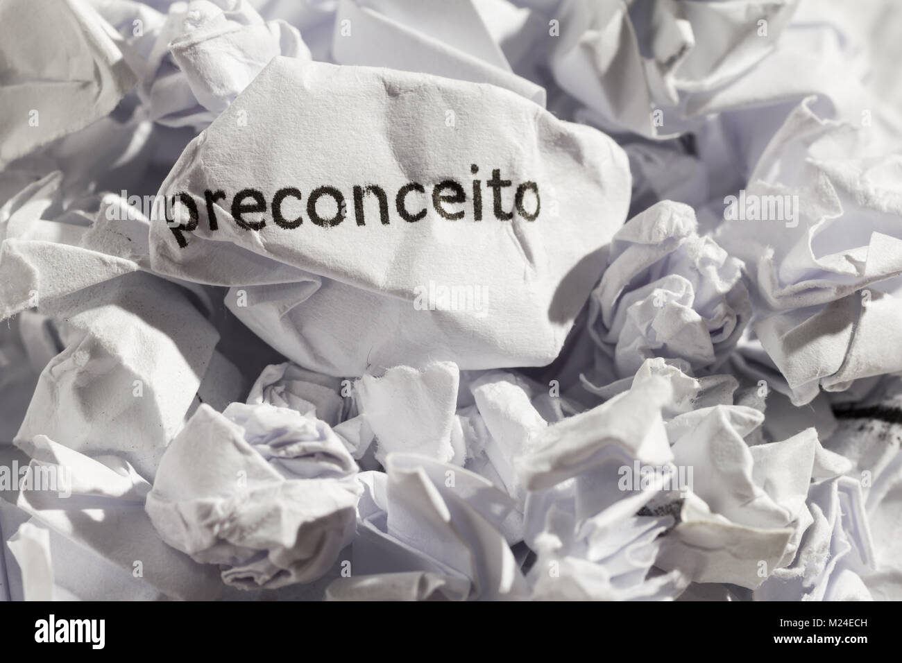 Crumpled paper written preconceito, portuguese word for prejudice. Illustrative concept of ideology thrown into Stock Photo