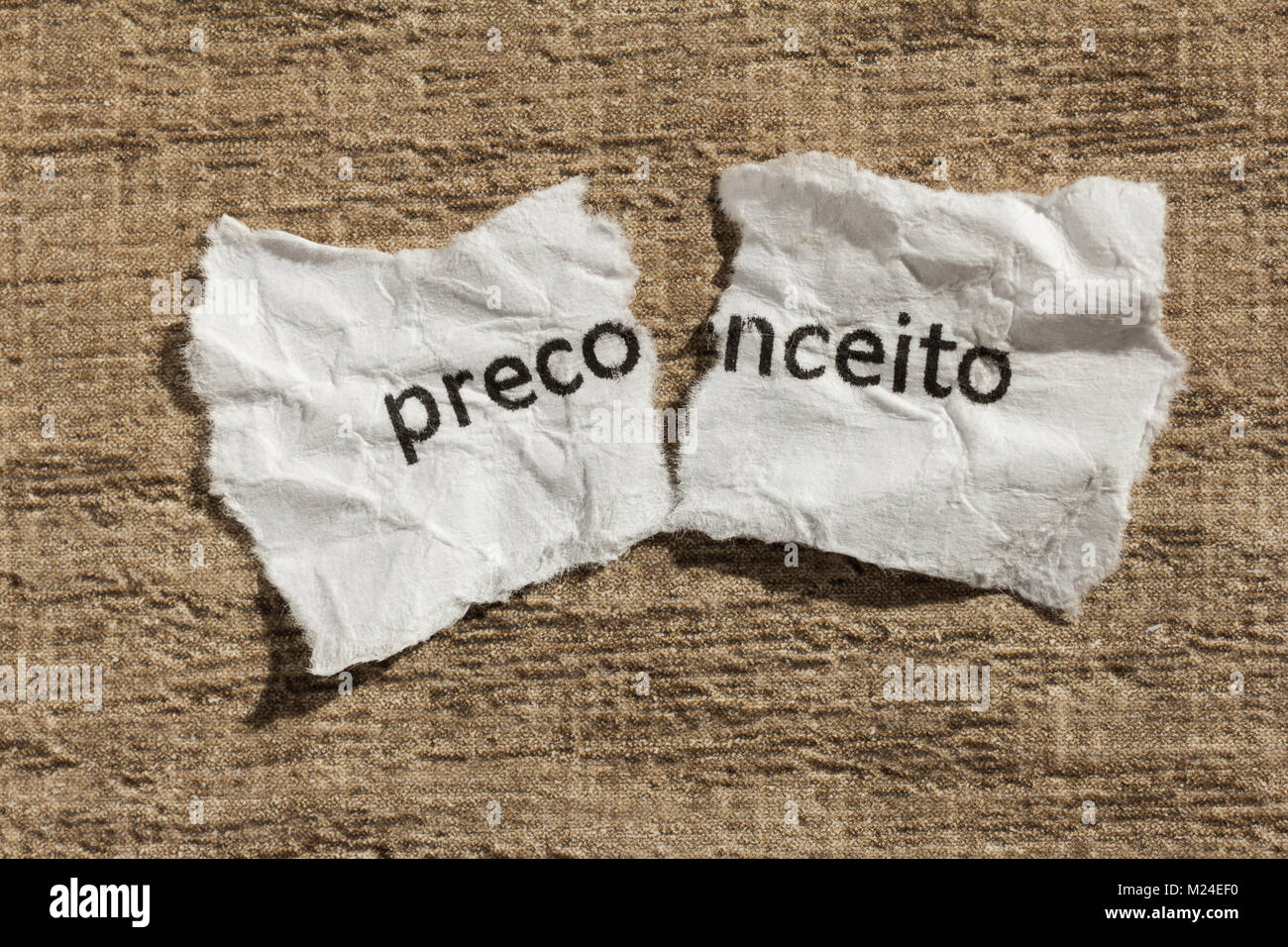 Torn paper written preconceito, portuguese word for prejudice, over wooden background. Old and abandoned idea or Stock Photo