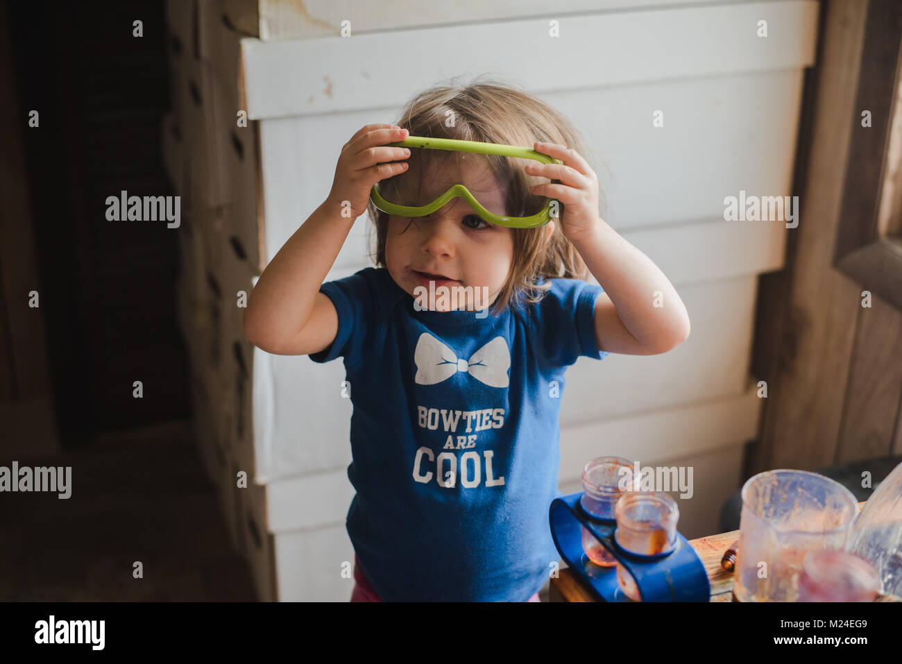 A 3-year old toddler girl works with science experiment equipment - Stock Image