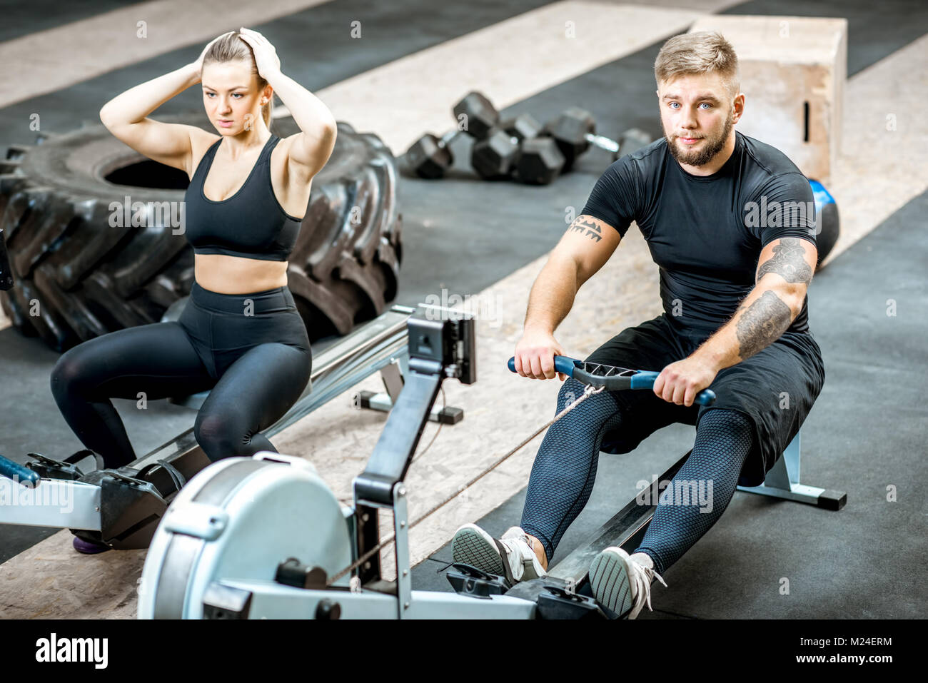 Couple training with exercise machines in the gym - Stock Image