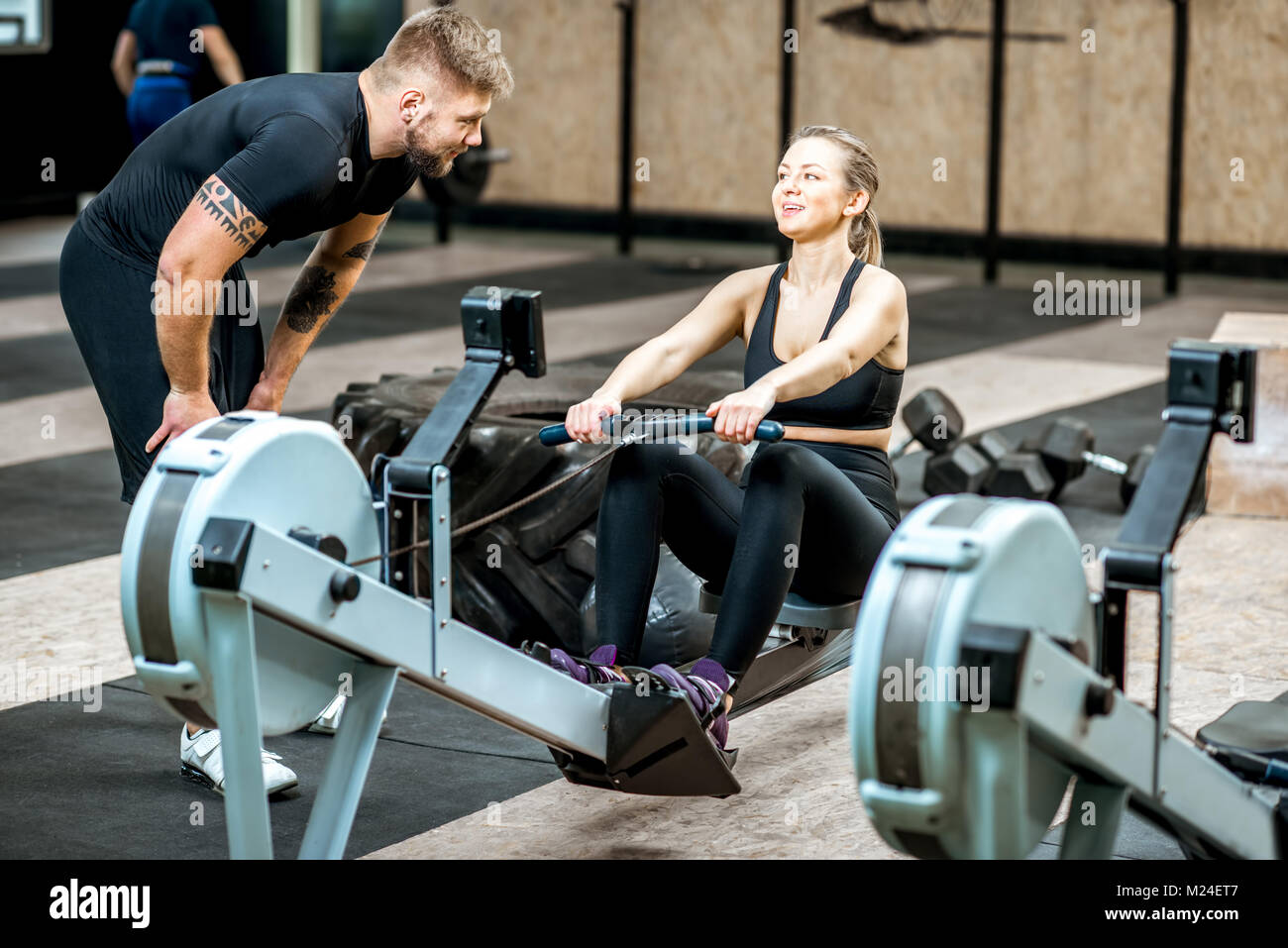 Coach training woman on the exercise machine - Stock Image