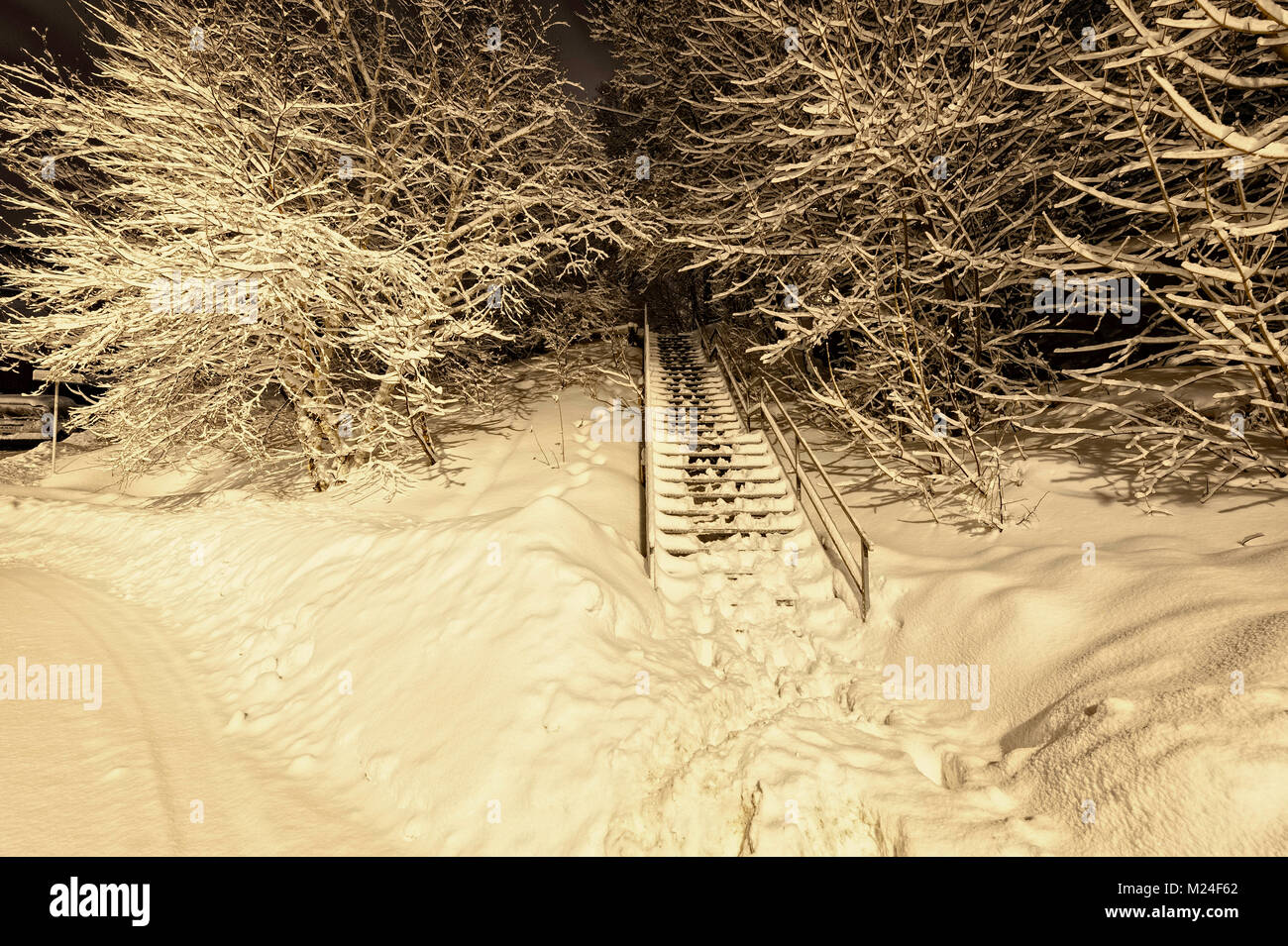 a snow covered stairway at night - Stock Image