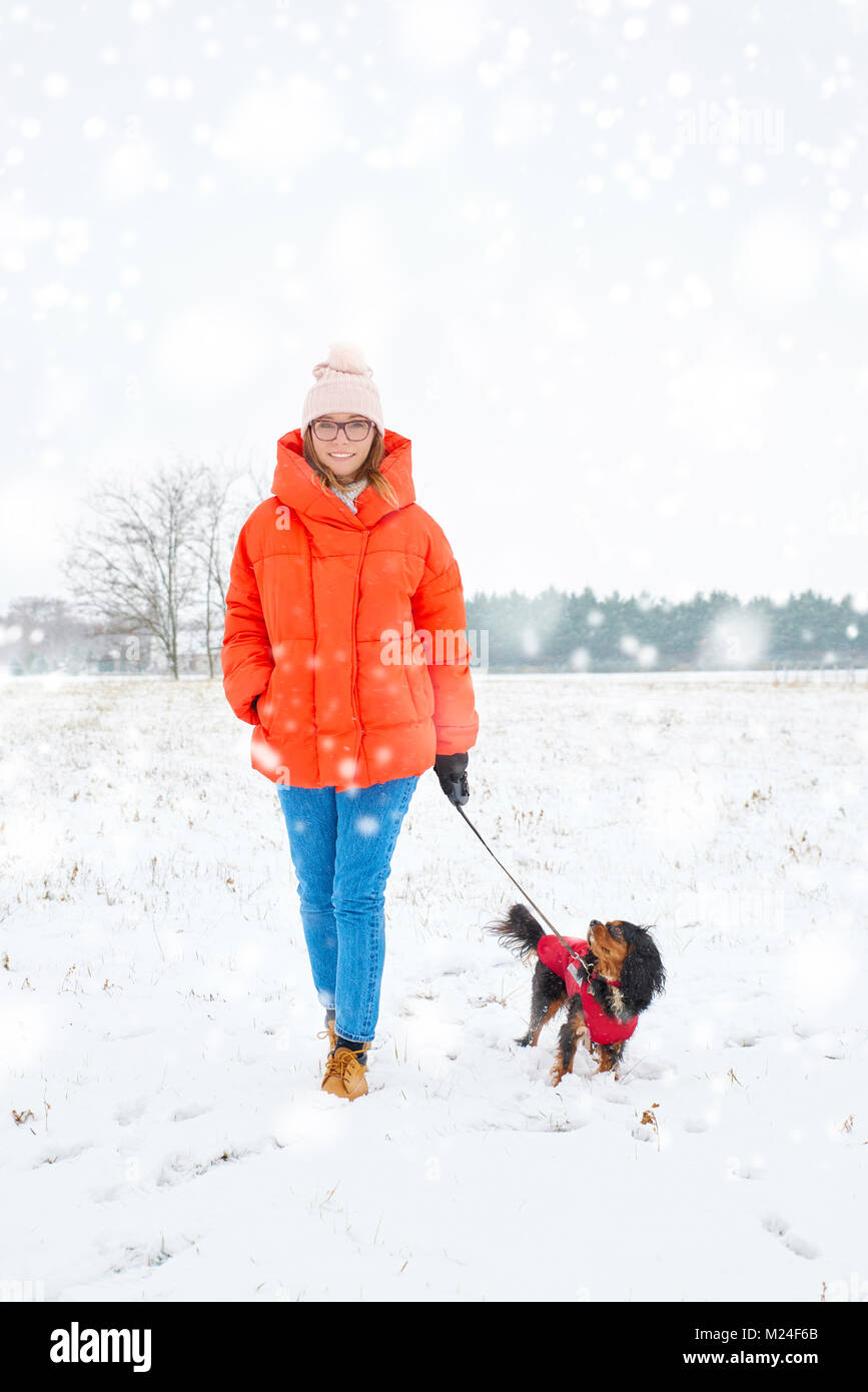 Full length shot of a happy woman walking her small dog outdoor in winter. - Stock Image