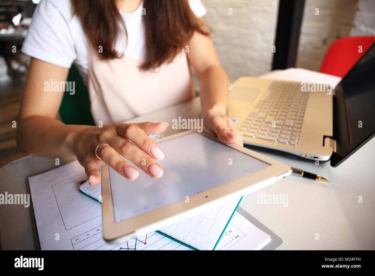 Smiling young woman using digital tablet in the office. Stock Photo