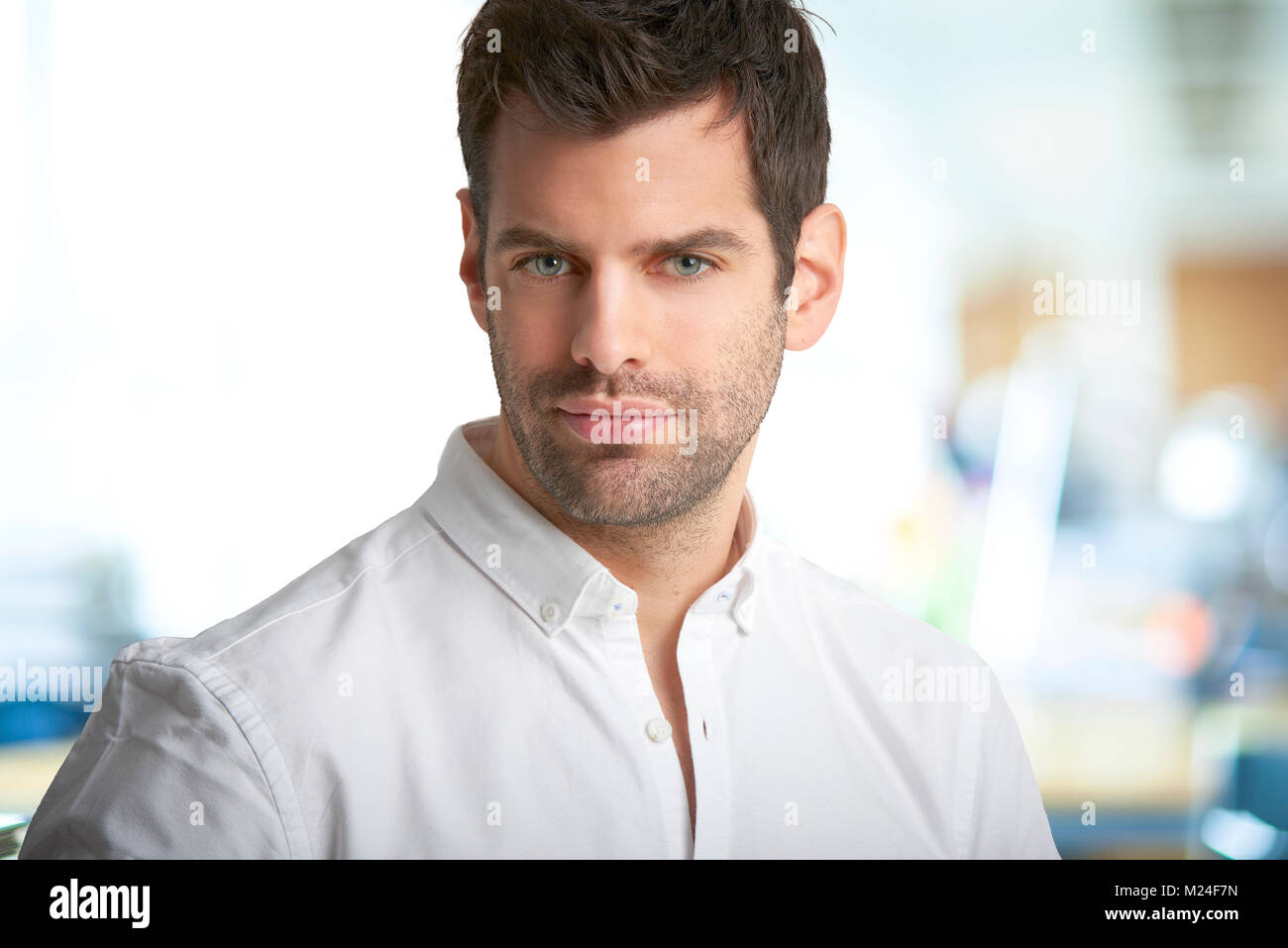 Close-up portrait of young financial assistant businessman looking at camera while standing at the office. - Stock Image