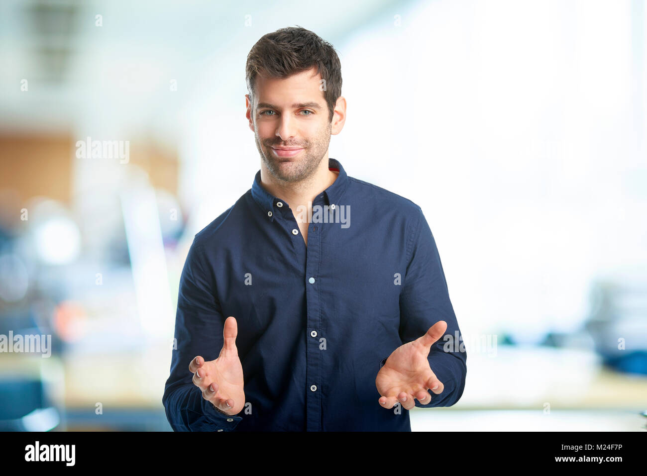 Portrait of smiling young businessman standing with his arms raised at the office. - Stock Image