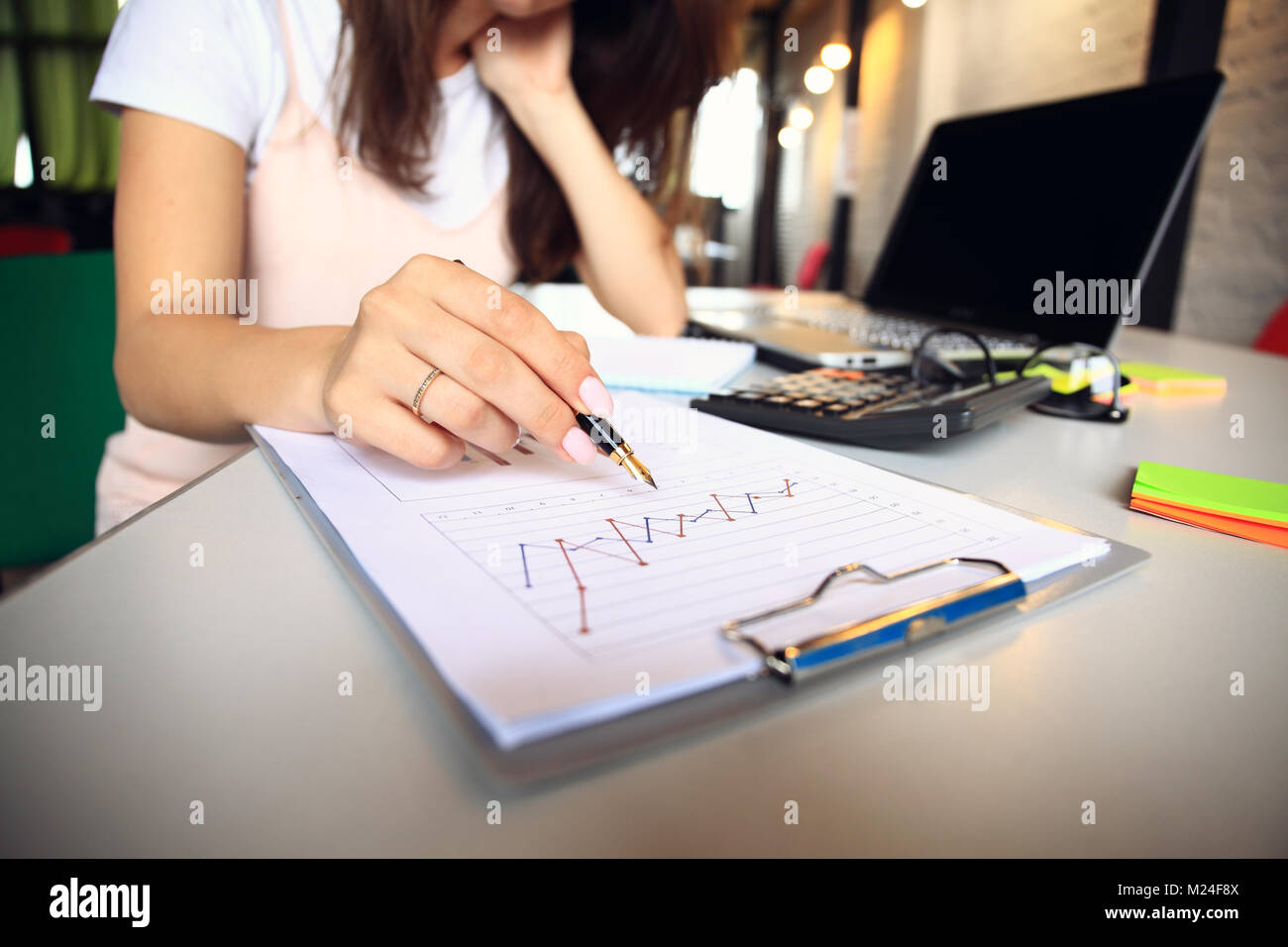 Close-up of female hand pointing at business document while explaining chart. - Stock Image