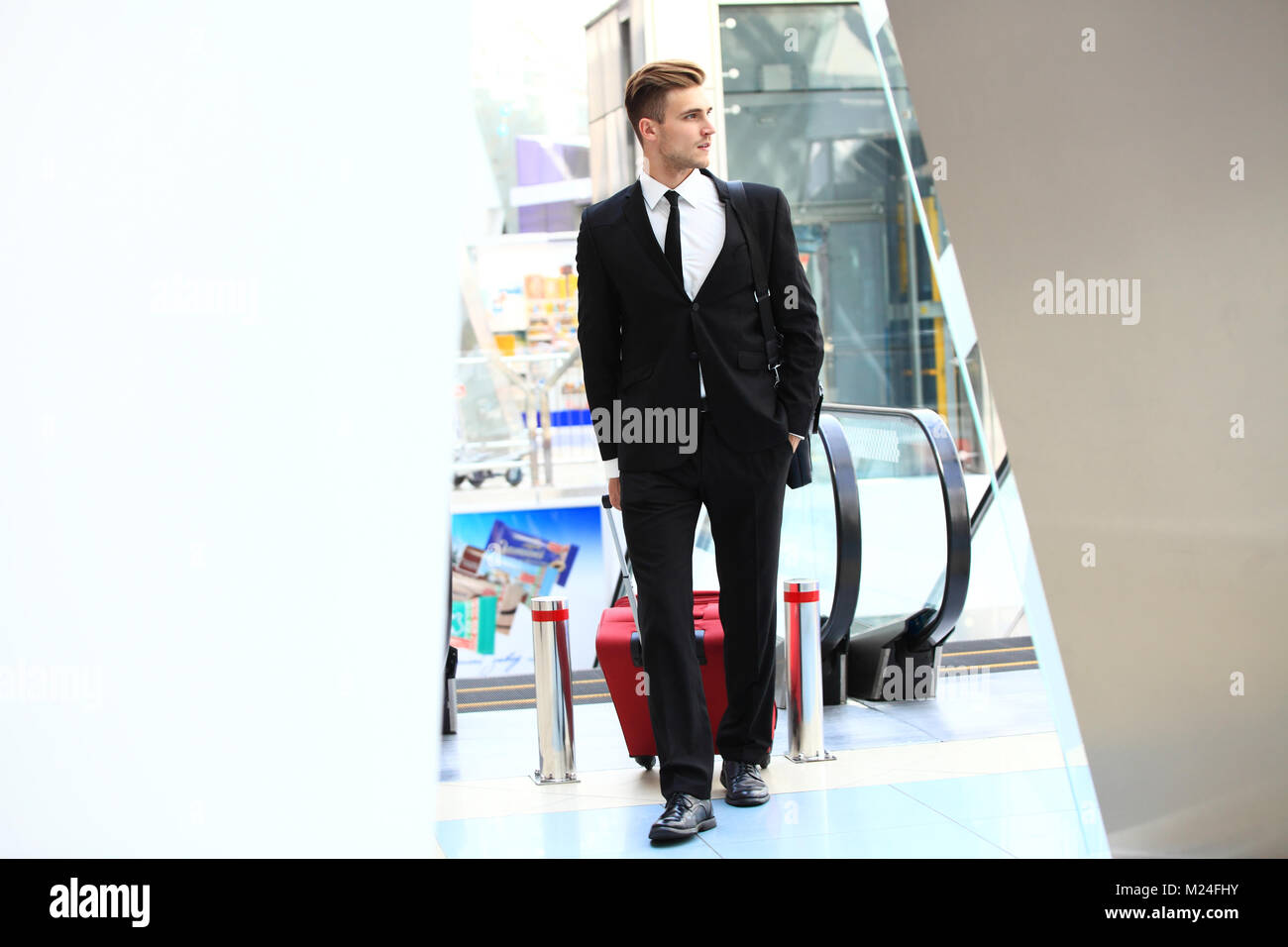 Business man at airport with suitcase - Stock Image