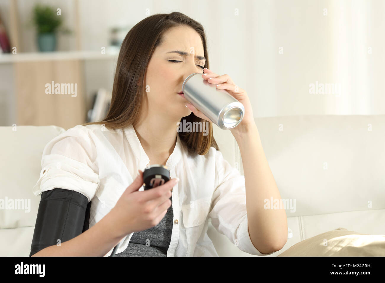 Woman suffering a low blood pressure drinking sweet soda sitting on a couch in the living room at home - Stock Image