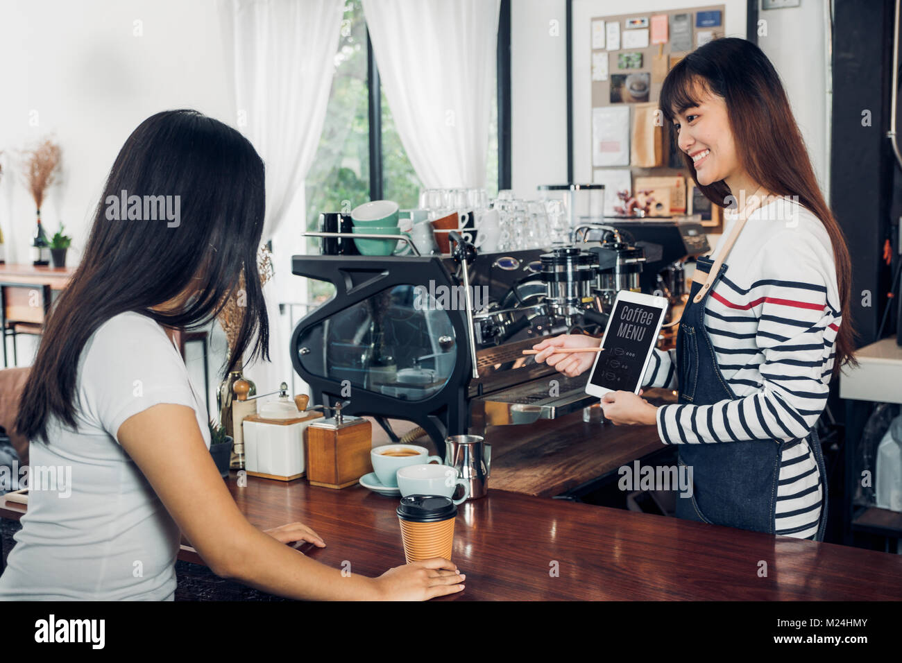 Asian woman barista wear jean apron suggestion coffee menu to customer at bar counter with smile emotion,Cafe restaurant - Stock Image