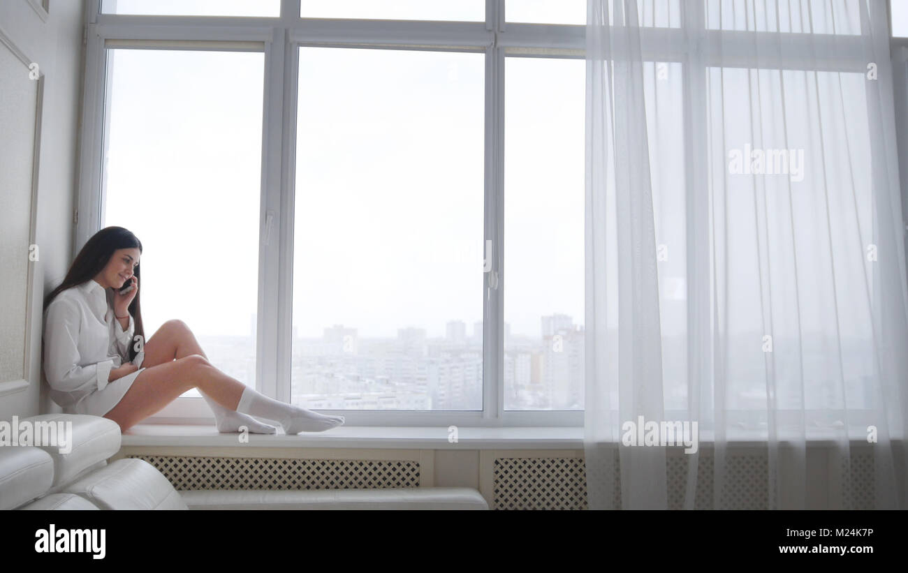 Beautiful young woman in a white men's shirt and socks sitting on windowsill, laughing and talking on the phone - Stock Image
