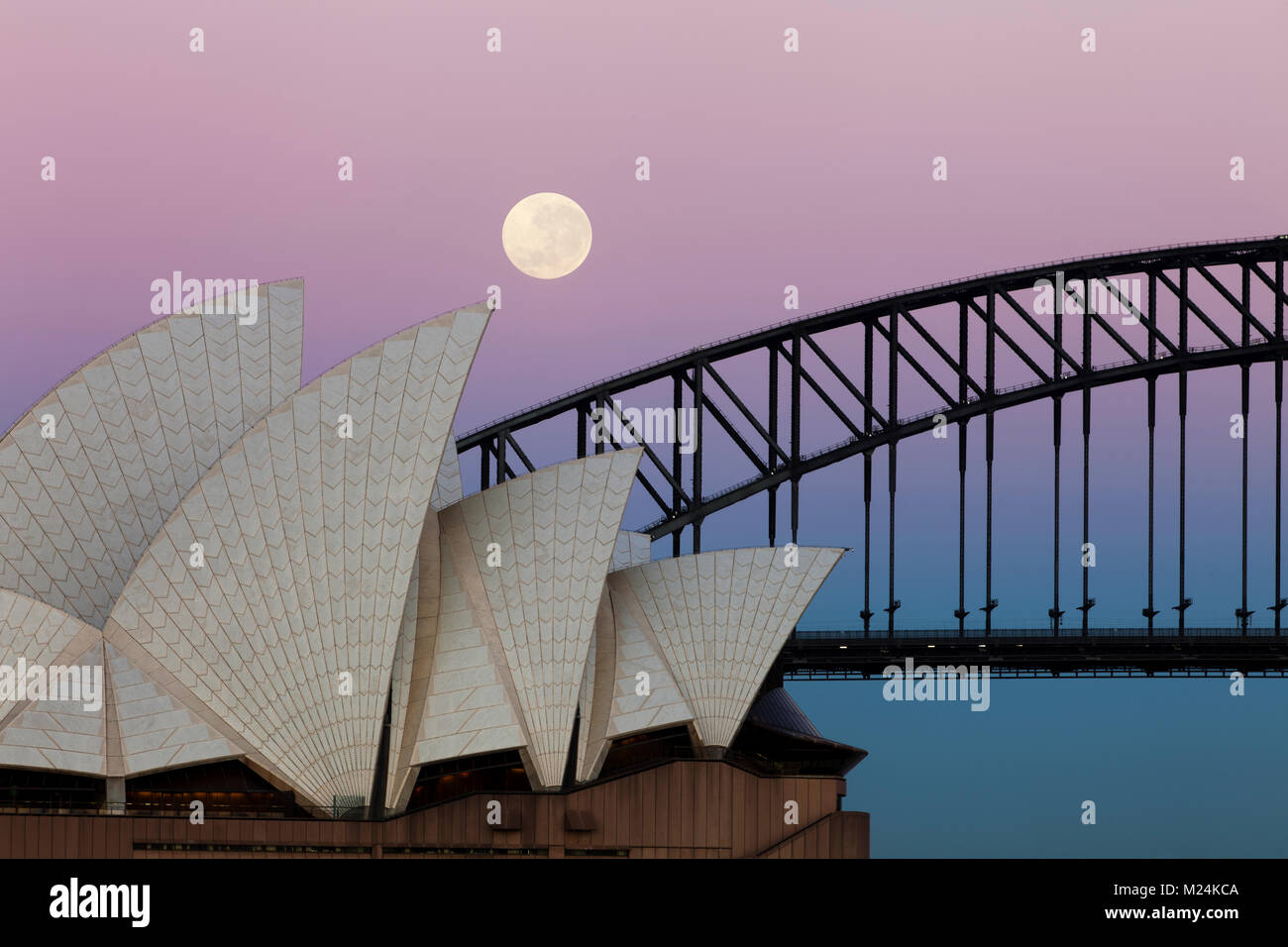 A full moon hovers over the Sydney Harbour Bridge and Opera House. The sky glows pink and blue as the sunrises. - Stock Image