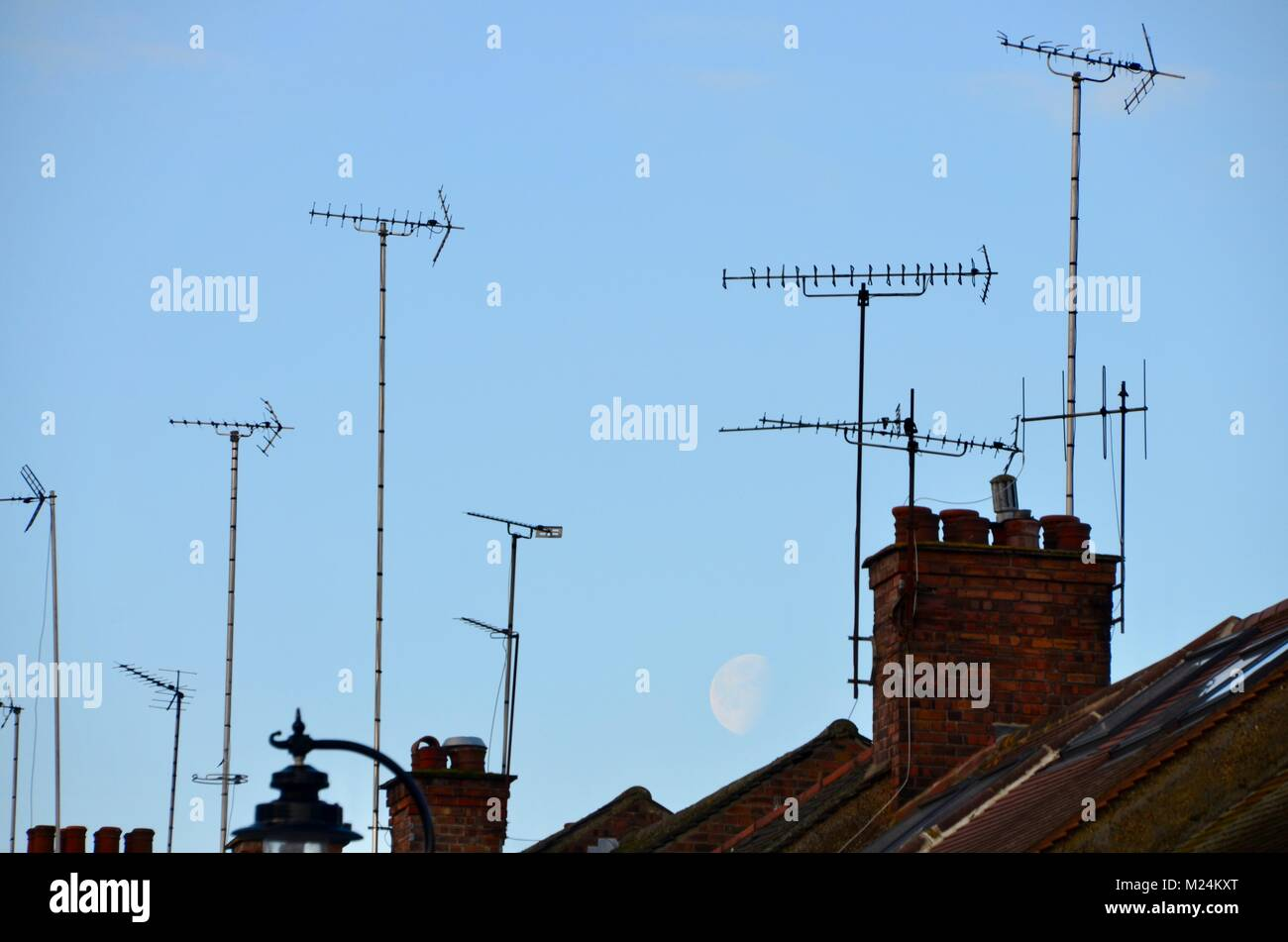 aerials and chimneys on london houses with a large moon behind - Stock Image