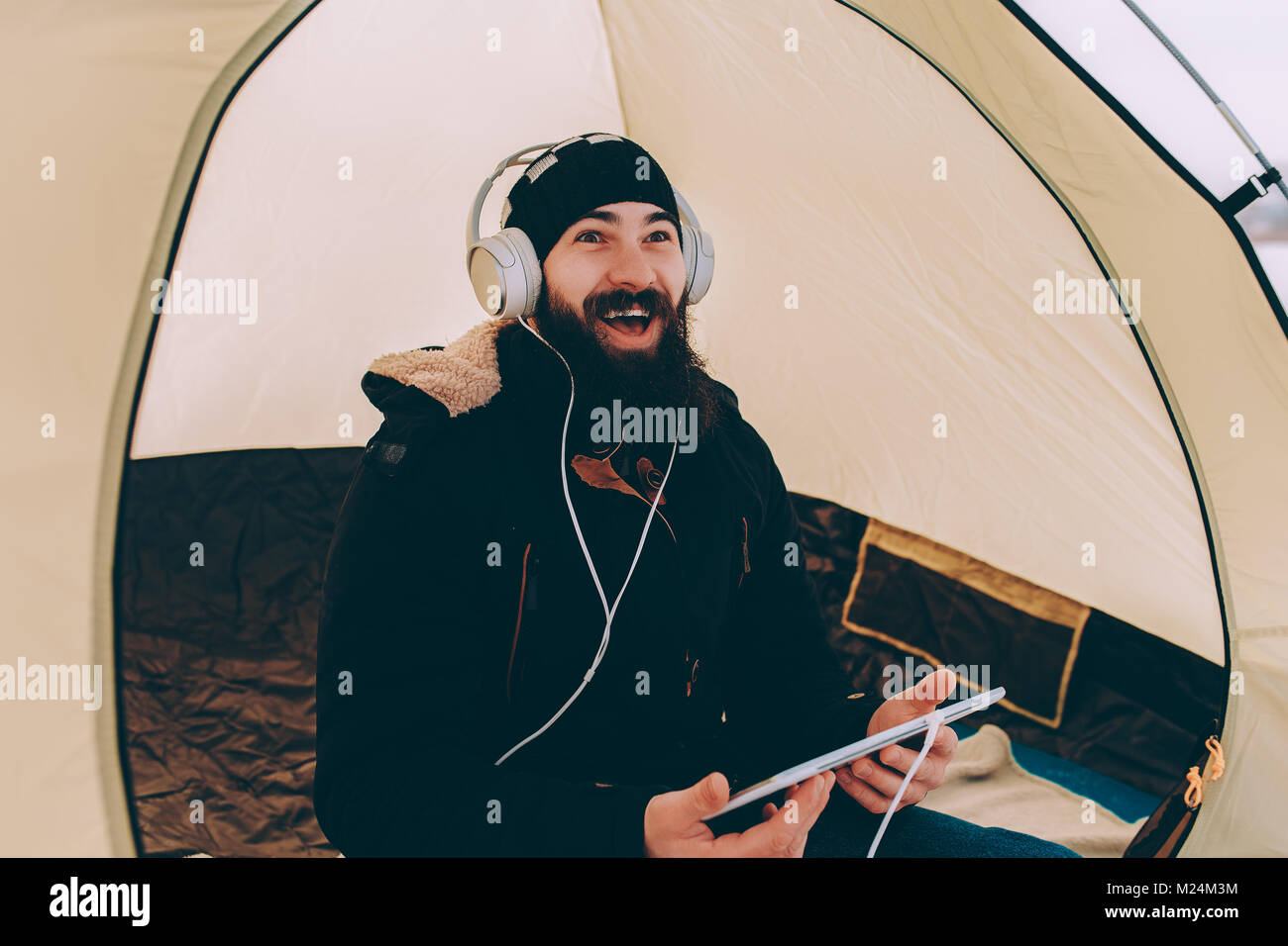 Bearded man with tablet laughing - Stock Image