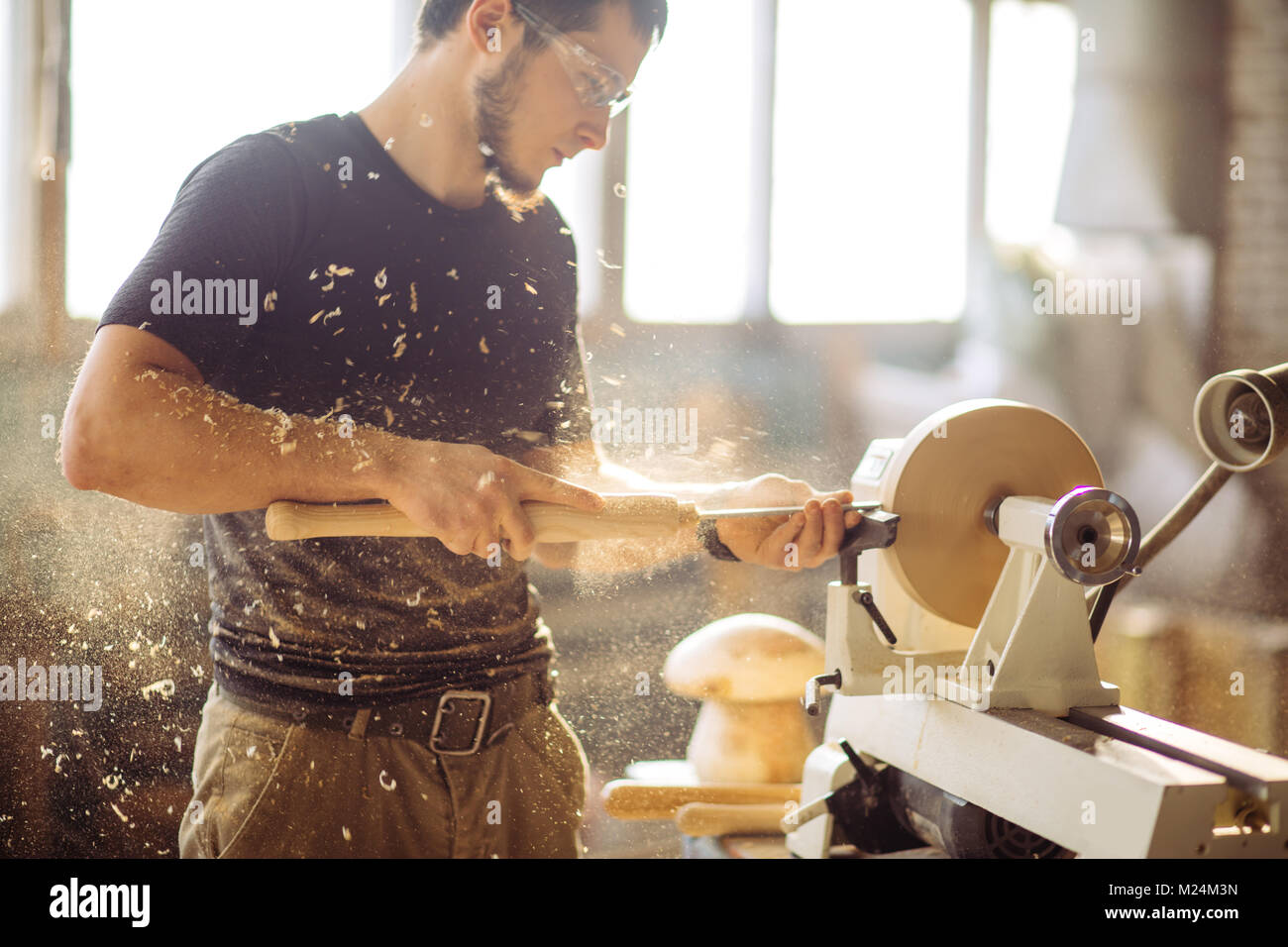 man working at small wood lathe, an artisan carves piece of wood - Stock Image