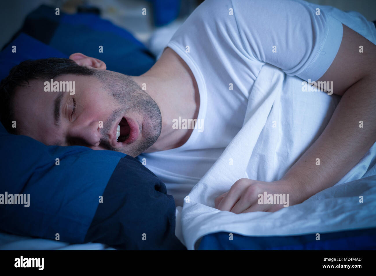 Portrait of man sleeping and snoring loudly lying in the bed - Stock Image