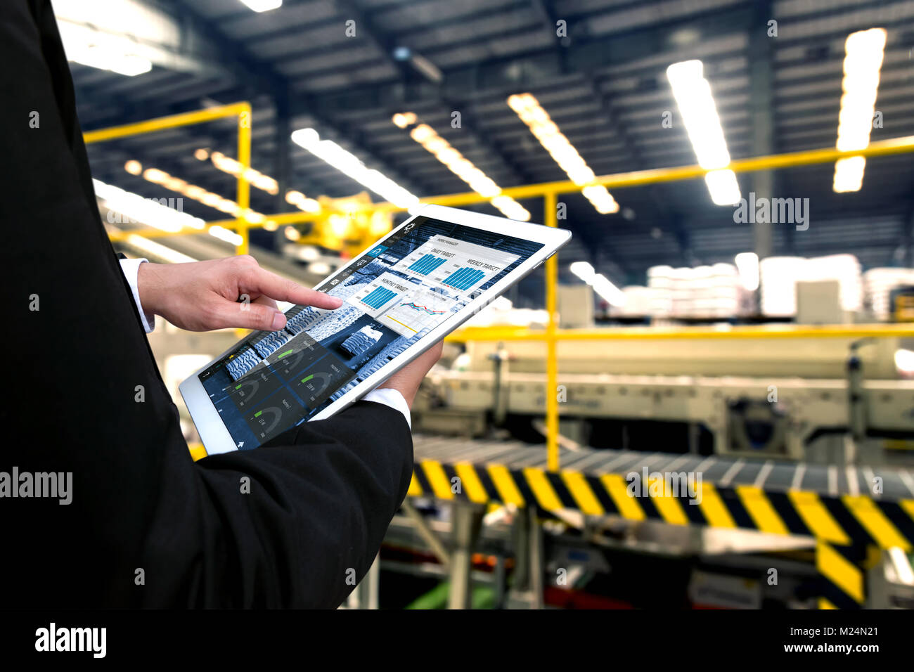 Engineer hand using tablet with machine real time monitoring system software. Automation robot arm , conveyor belt - Stock Image