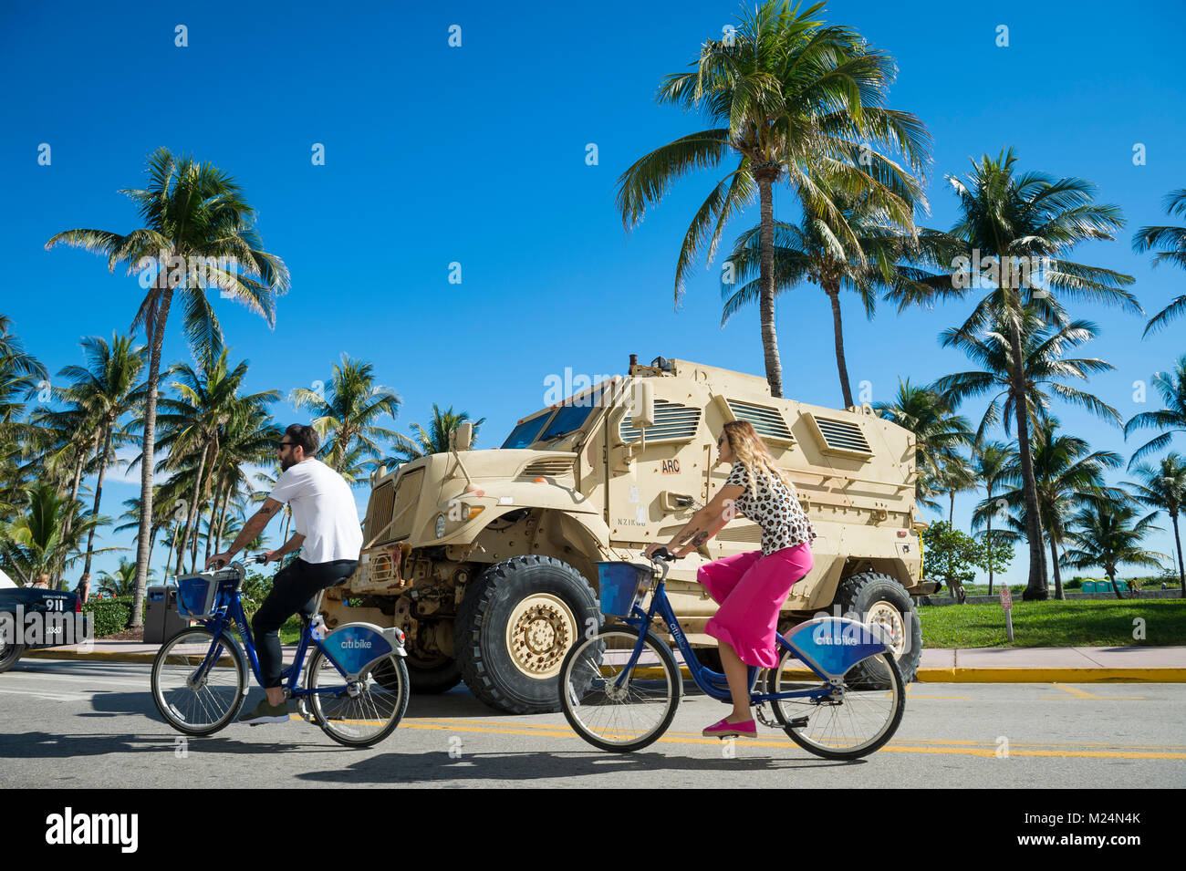 MIAMI - DECEMBER 29, 2017: Cyclists pass a large armored military vehicle stationed on Ocean Drive as security is - Stock Image