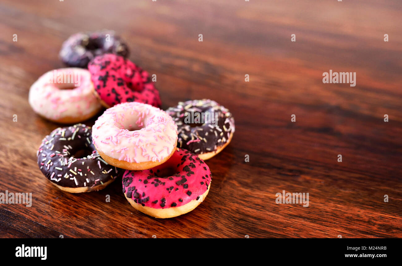 delicious chocolate donuts or fresh donut with glaze or icing and sprinkles. Variation or arrangement of sweet food - Stock Image