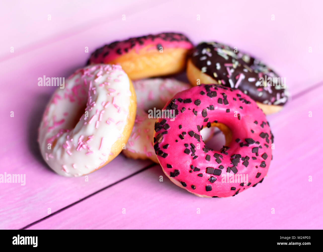 Delicious glazed donuts with sprinkles. Pink table and arrangement of chocolate donuts, various donuts, sweet food - Stock Image