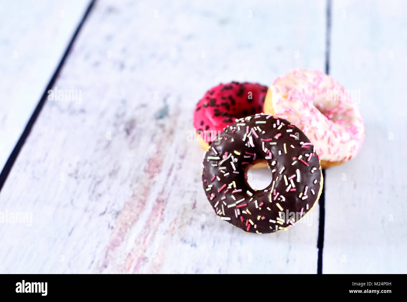 delicious donuts with glaze or icing and sprinkles. variation of fresh donuts on a white wooden table. Arrangement - Stock Image