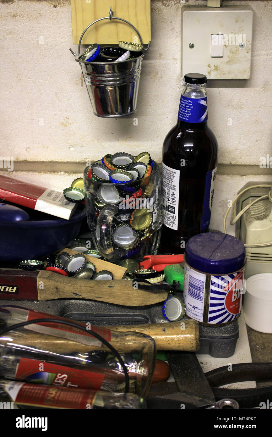 Beer bottles and tops that have collected in a dimpled pint pot and have spilled out amongst the tools on a bench - Stock Image