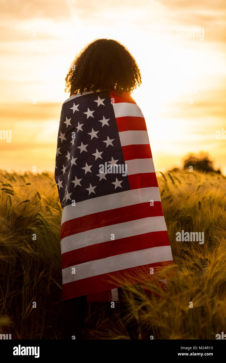 Vintage style photograph of mixed race African American girl teenager female young woman in a field of wheat or Stock Photo