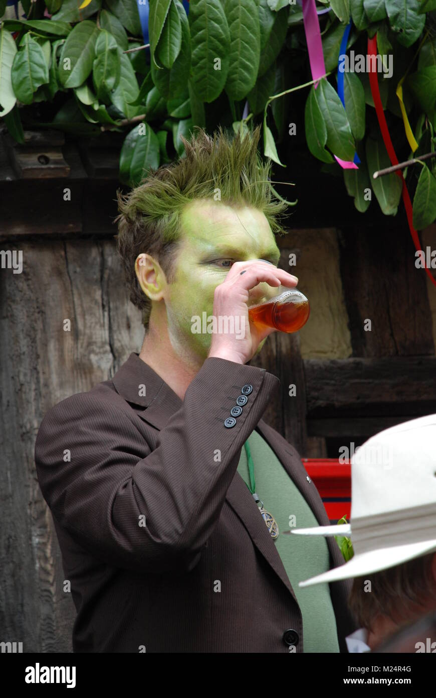 A male festival goer with green dyed face drinks a beer at the Jack In The Green festival at Hastings in East Sussex, - Stock Image