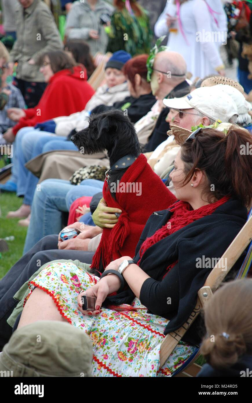 Festival goers sit in deck chairs on the West Hill at the annual Jack In The Green festival at Hastings in East Stock Photo