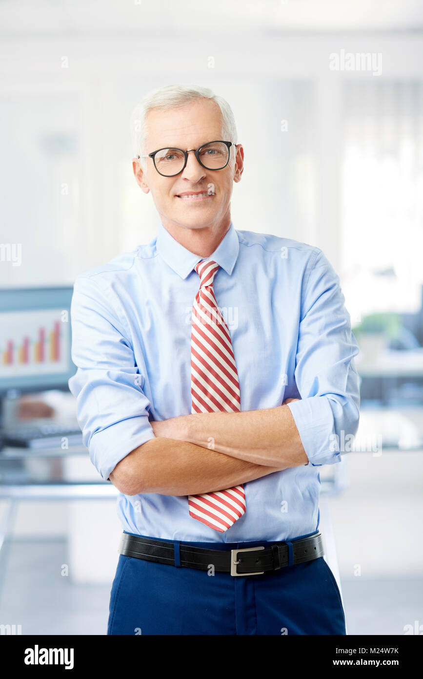 An executive senior financial advisor businessman standing with arms crossed at the office and looking at camera. - Stock Image