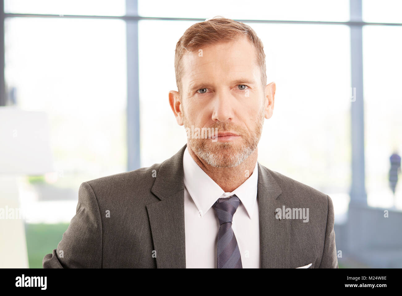 Close-up portrait of sales businessman looking at camera while standing at the office. - Stock Image