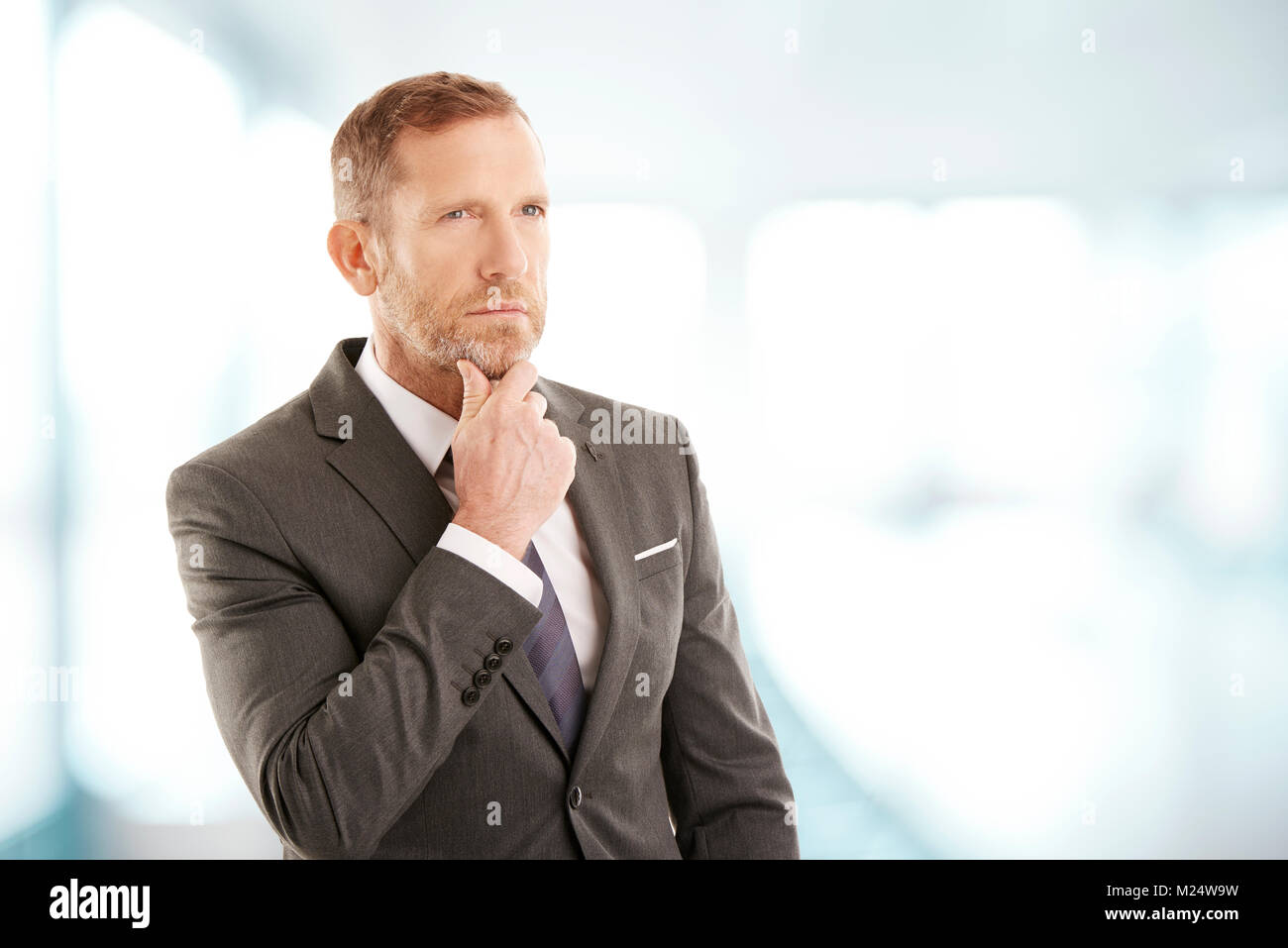 Middle aged businessman wearing suit while standing at the office and seemd deep in thought. Professional man looking - Stock Image