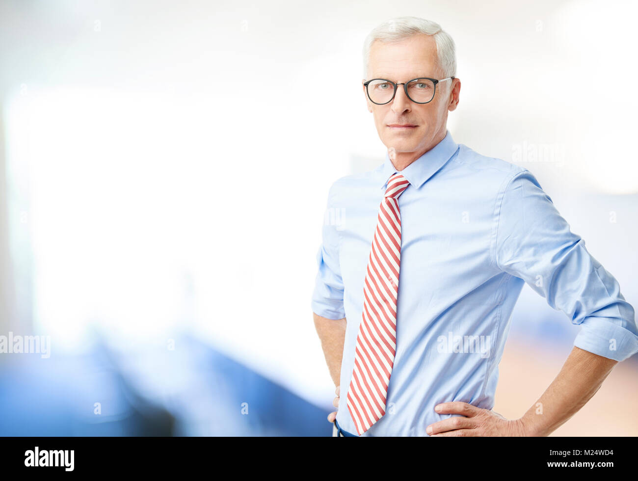 Senior professional man standing with hands on his hips in the office and looking at camera. - Stock Image