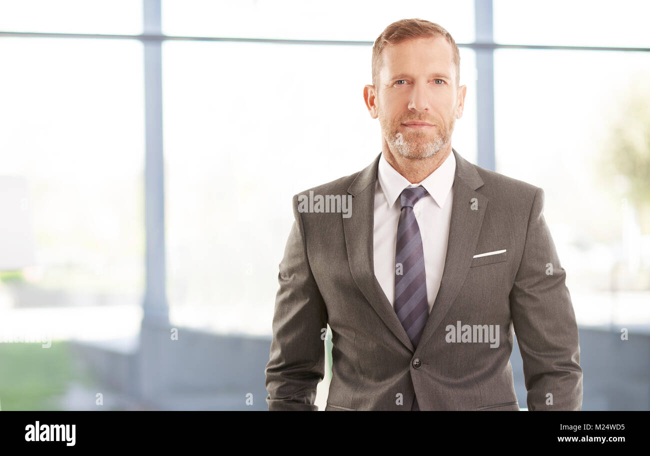 Smiling executive financial director businessman standing at the office. - Stock Image