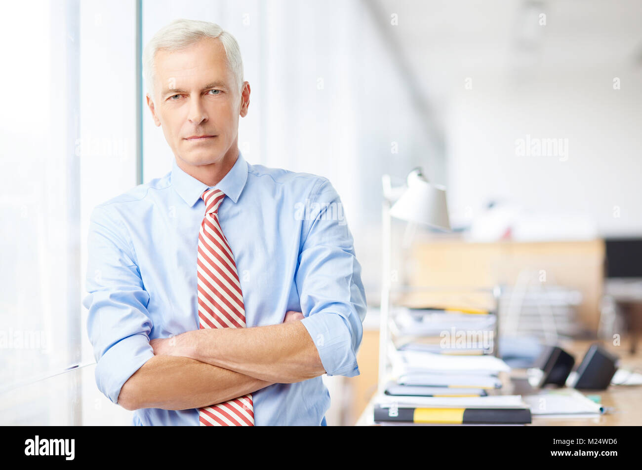 An executive sales manager standing with arms crossed at the office and looking at camera. - Stock Image
