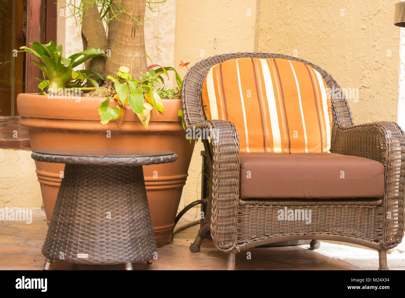 Wicker Chair with Orange striped cushion and terra cotta planter Stock Photo