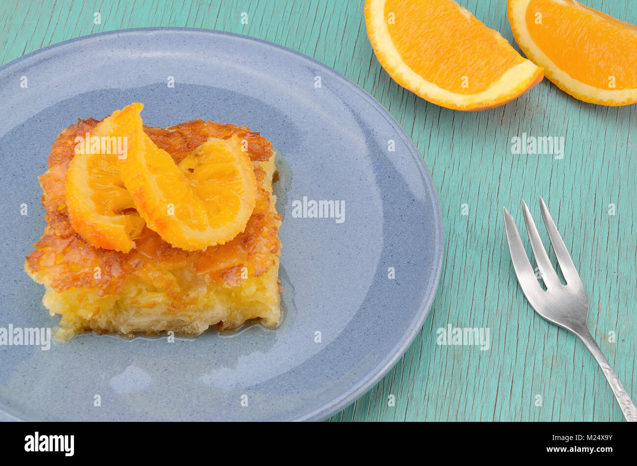 Piece of orange pie in plate with orange twist slice on top and two orange pieces Stock Photo
