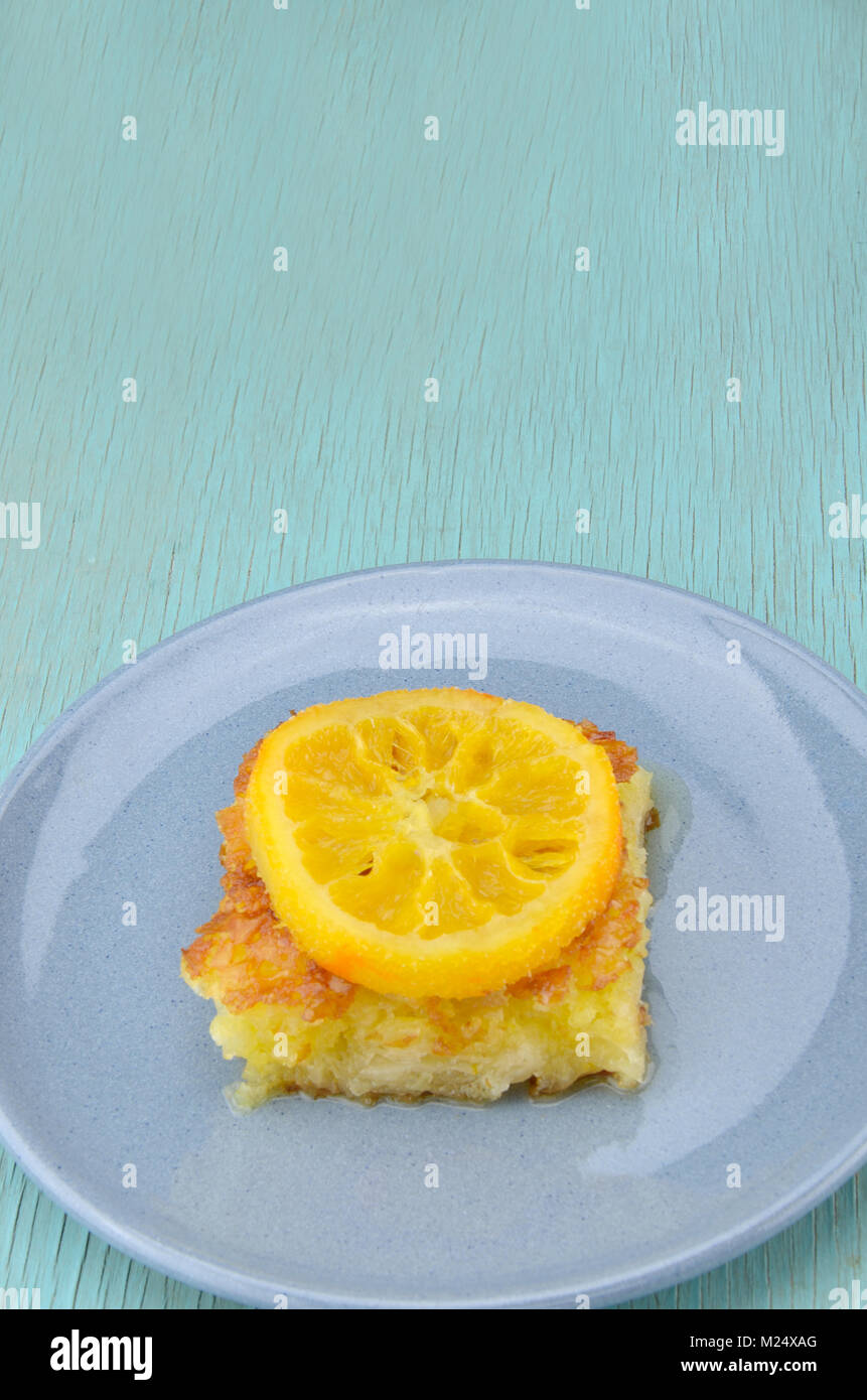 Piece of orange pie in plate with orange  slice on top Stock Photo