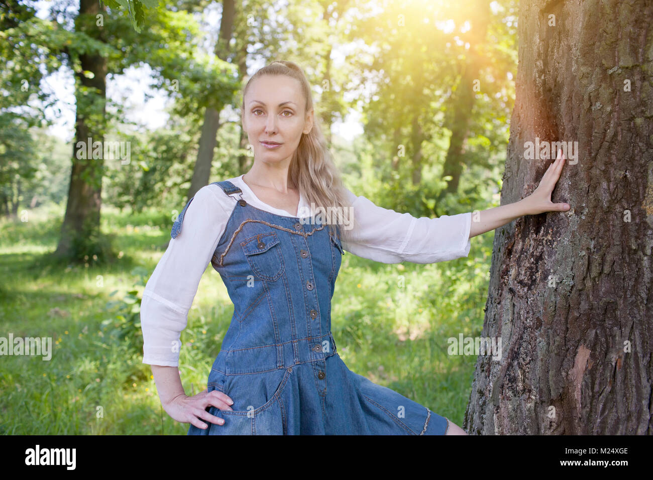 beautiful slender young woman in a blue sundress and a white blouse near a birch - Stock Image
