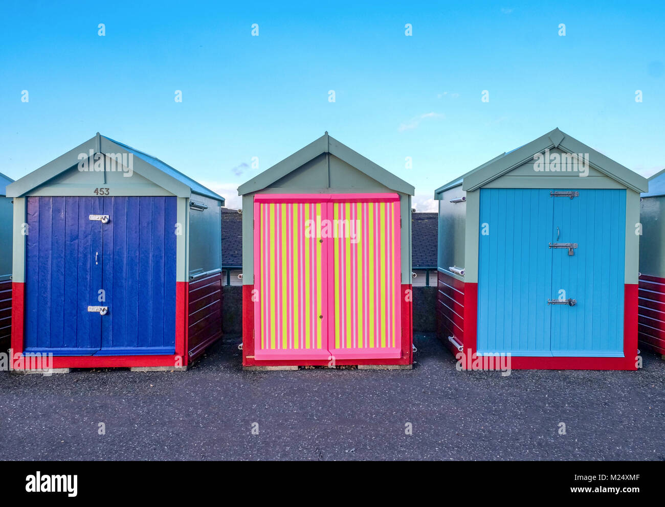 Brighton seafront three beach huts, two with blue doors and the one in the middle has a multi coloured door of yellow, - Stock Image